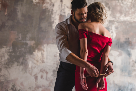 Foto de handsome young man putting handcuffs on seductive woman in red dress - Imagen libre de derechos
