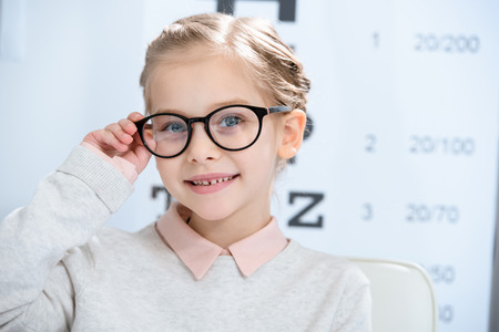 Photo pour adorable smiling child looking at camera in glasses at oculist consulting room - image libre de droit