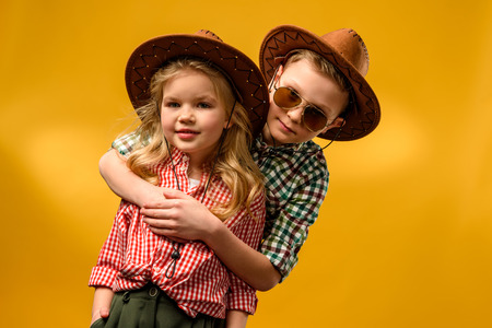 Foto de little stylish cowboy and cowgirl in hats hugging isolated on yellow - Imagen libre de derechos