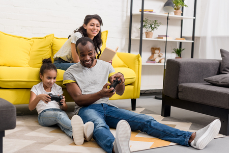 Photo pour Happy father and daughter playing video games while mother sitting on couch - image libre de droit
