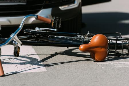 Photo pour Close up view of broken bicycle and car on road, car accident concept - image libre de droit