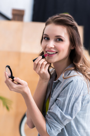 Photo pour Beautiful young woman applying makeup and smiling at camera - image libre de droit