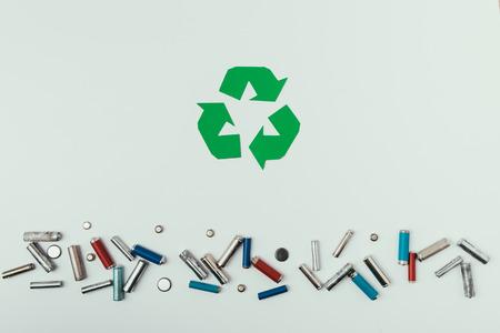 Foto de Top view of recycle sign and various types of batteries isolated on grey - Imagen libre de derechos