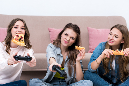Beautiful young women eating pizza and playing with joysticks
