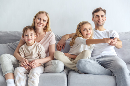 Photo pour happy young family watching movie at home on weekend - image libre de droit