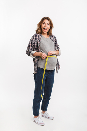 excited pregnant woman measuring tummy with measuring tape isolated on grey