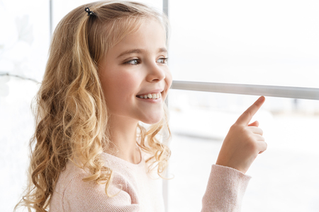 Photo pour smiling little child pointing at window - image libre de droit