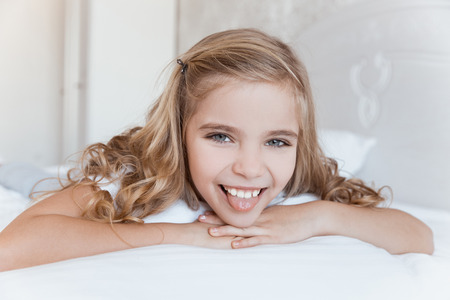 Photo pour smiling kid lying on bed and sticking tongue out - image libre de droit
