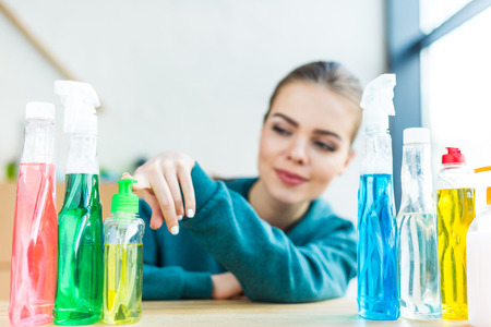 Photo pour smiling young woman looking at various plastic bottles with cleaning products - image libre de droit