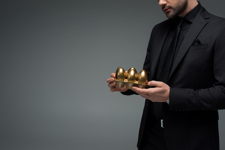 Foto de Cropped image of male holding golden eggs isolated on grey, easter concept - Imagen libre de derechos