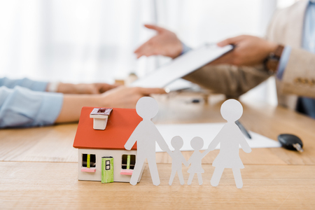 Photo for White paper cut family and house model on wooden table with blurred people at background, life and house insurance - Royalty Free Image