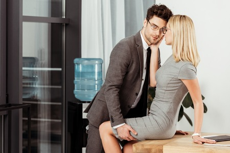 Photo pour Side view of business colleagues flirting at workplace in office, office romance concept - image libre de droit