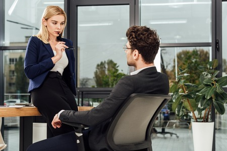 Photo pour Attractive businesswoman flirting with business colleague at workplace in office - image libre de droit