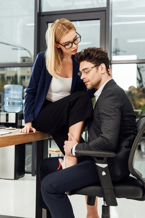 Photo pour young businesswoman flirting with business colleague at workplace in office - image libre de droit