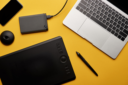 Foto de Top view of various graphic designer gadgets on yellow surface - Imagen libre de derechos