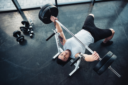 Top view of concentrated sportsman training with barbell at gym