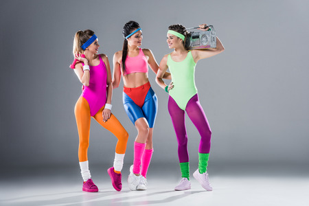 Foto de attractive sporty girls with dumbbells and tape recorder smiling each other on grey - Imagen libre de derechos