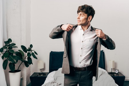 Photo pour Side view of handsome businessman putting on jacket in bedroom at home - image libre de droit