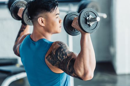 Focused young sportsman exercising with dumbbells in gym