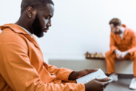 Foto de Side view of African american prisoner reading book - Imagen libre de derechos