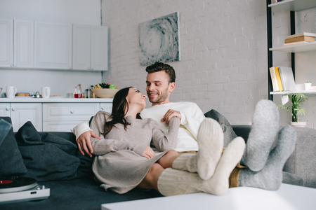 Photo pour happy couple in woolen socks relaxing on couch at home - image libre de droit