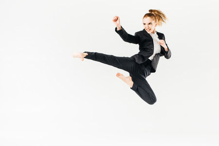 Foto de businesswoman screaming, jumping and performing kick in suit isolated on white - Imagen libre de derechos