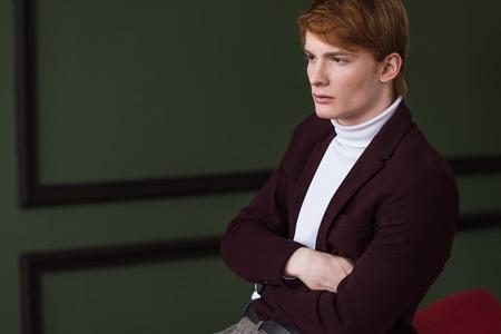 Foto de Side view of male model in jacket sitting on couch - Imagen libre de derechos