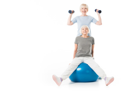 Foto de Two senior sportswomen with fitness ball and dumbbells isolated on white - Imagen libre de derechos