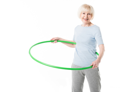 Photo for Senior sportswoman doing hula hoop exercise isolated on white - Royalty Free Image