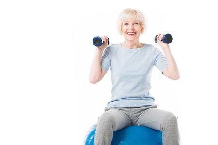 Foto de Senior sportswoman with dumbbells sitting on fitness ball isolated on white - Imagen libre de derechos
