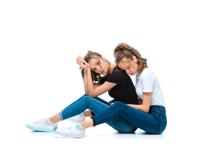 Photo pour attractive young twins sitting of floor on white - image libre de droit