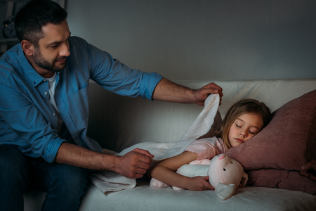 Foto de father covering sleeping daughter with blanket - Imagen libre de derechos