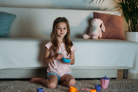 Photo for little kid pretending ti have tea party while sitting on floor at home - Royalty Free Image