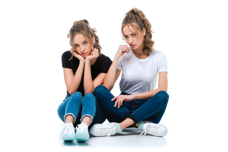Photo for attractive young twins sitting on floor and looking at camera on white - Royalty Free Image