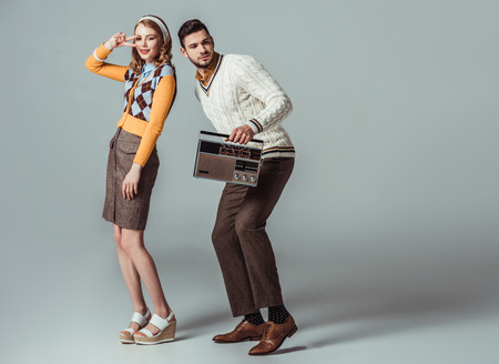 Photo pour beautiful retro styled couple dancing with vintage radio on grey - image libre de droit