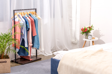 Photo pour interior of modern bedroom with hanger full of various female clothing - image libre de droit