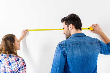 Photo for girlfriend and boyfriend measuring wall with tape measure - Royalty Free Image
