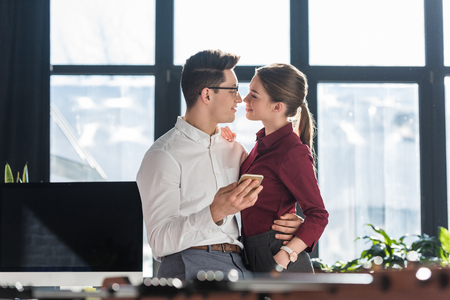Photo pour attractive kissing young businesspeople in formal clothing having office romance - image libre de droit