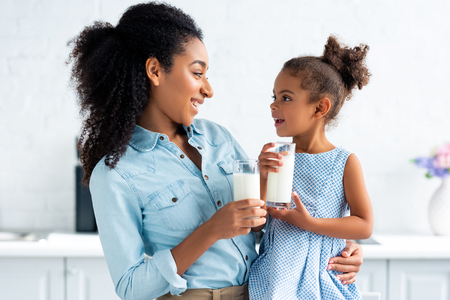 Foto de cheerful african american mother and daughter holding glasses of milk in kitchen and looking at each other - Imagen libre de derechos