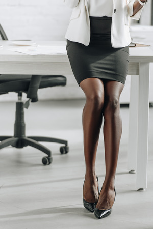 Photo pour cropped view of legs of african american businesswoman in formal wear in office - image libre de droit