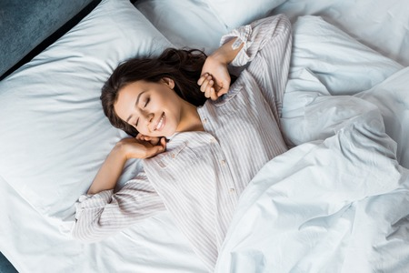 Foto de attractive young woman in pajamas waking up in bed in the morning - Imagen libre de derechos