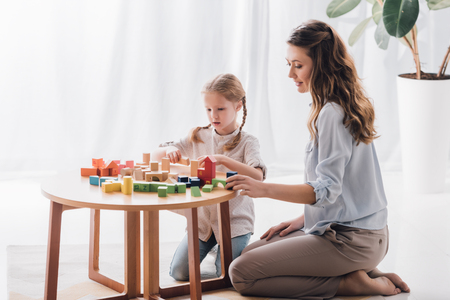 Photo pour Side view of happy mother playing blocks with adorable little child - image libre de droit