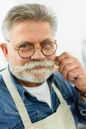 Photo pour Cheerful middle aged male craftsman in apron looking at camera in studio - image libre de droit