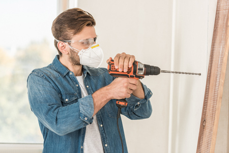 Foto de Young man in protective mask and goggles using electric drill during house repair - Imagen libre de derechos