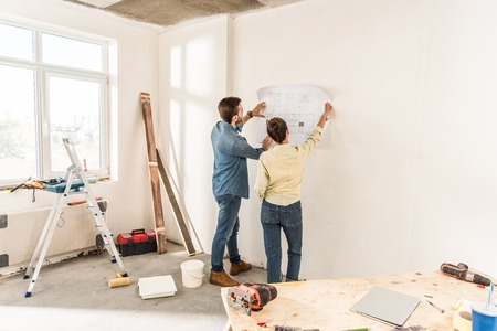 Photo pour Back view of young couple holding blueprint at wall during repairment - image libre de droit