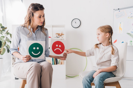 Foto de Adult psychologist showing happy and sad emotion faces cards to child - Imagen libre de derechos