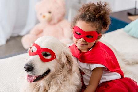 Photo pour Smiling adorable little african american kid with happy dog in red superhero mask - image libre de droit