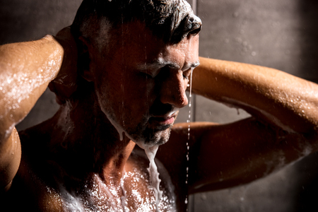 Foto de Close up view of adult man with closed eyes washing foam in shower - Imagen libre de derechos