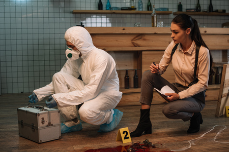 Photo for Forensic investigator and focused female detective taking notes and examining crime scene together - Royalty Free Image