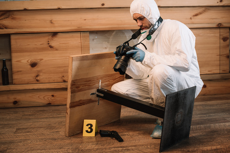 Photo for Forensic investigator documenting evidence with camera at crime scene - Royalty Free Image
